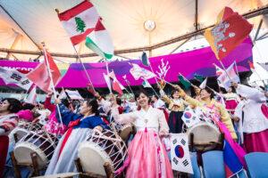 民族衣装(チマチョゴリ)で早くから会場に集まり、さまざまな国旗を手に多くの選手へエールを贈る韓国の人々