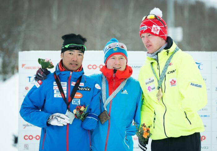 2月15日スプリント・クラシカル、スタンディングクラスの表彰式。1位ブラディスラフ・レコムチェフ(ロシア20歳)、2位・新田佳浩(日立ソリューションズ34歳)、3位マーク.アレンズ(カナダ24歳)