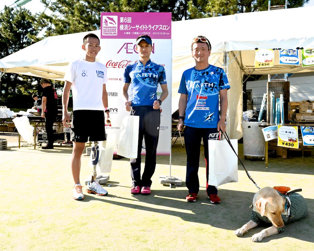 表彰式を終えた、パラトライアスリート。左から、中山賢史朗(大腿切断)、ガイドの高瀬誠、中澤隆(視覚障害B2)、介助犬デネブ