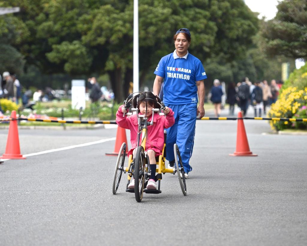 ハンドバイクを体験する子供と横浜市スポーツ文化センターラポールのスポーツ指導員・山川洋氏