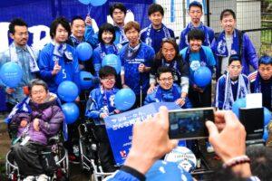 電動車椅子サッカーの選手たちを記念撮影する来場者
