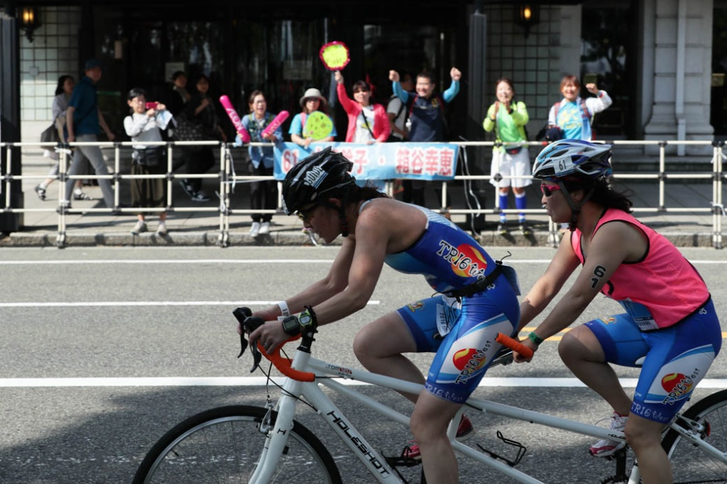 エイジパラトライアスロン、自転車のパート。ガイドの箱谷さん(前)と走る 写真・佐々木延江