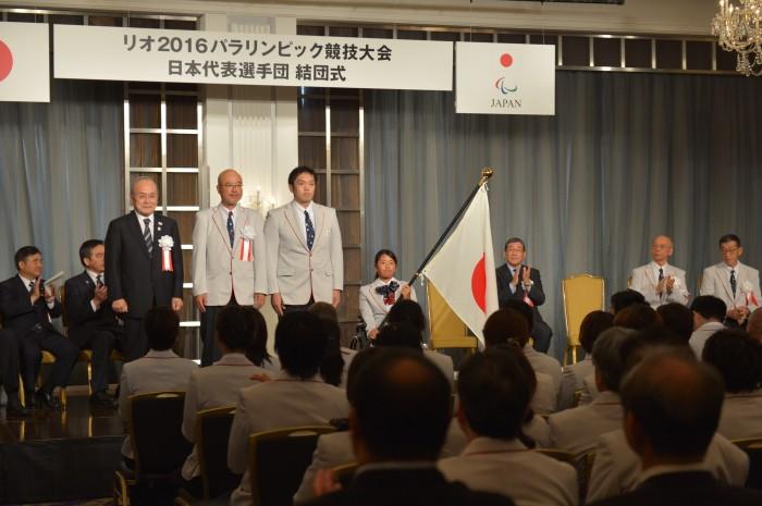 団旗が鳥原光憲JPC(日本パラリンピック委員会)会長から、団長・大槻洋也、主将で車いすバスケットボールの藤本怜央(SUS)、騎手で車いすテニスの上地結衣(エイベックス)へと授与された