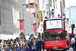 パラリンピックのフラッグがはためく選手を乗せたバス