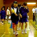 高齢者の体験で、体に重りなどをつけて歩く生徒(左)