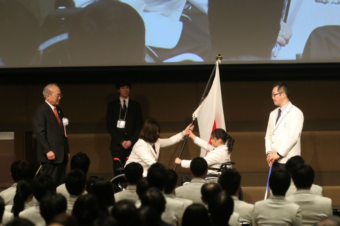 団旗授与。大日方団長から、旗手の村岡桃佳へ 写真・内田和稔