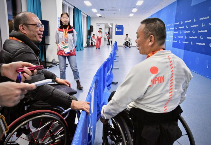 アイスホッケーの会場でインタビューする北海道新聞社の永瀬充記者。TMAで移動する情報をくれた (写真・佐々木延江)
