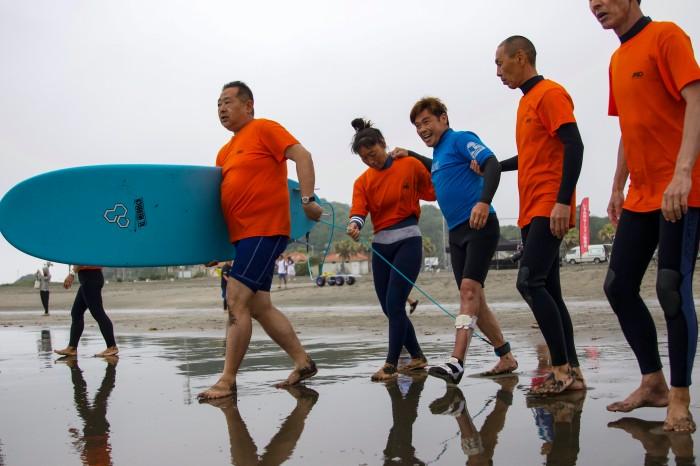 ボランティア・スタッフのサポートで海に向かう選手 (写真・吉田直人)
