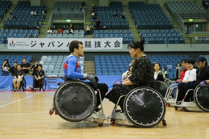 ブレイクタイムの体験コーナーでフランス選手のタックルを受ける専門学校生の長谷川さん(写真・内田和稔)