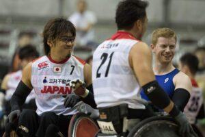 26日、大会2度目になる日本-イギリス戦で。ともに1勝1敗のこの2チームで最終日の決勝戦を戦う。日本のエース池崎大輔(左)と背番号21番・池透暢の背中を挟んでイギリスチームのJim Roberts (写真・水口之孝)