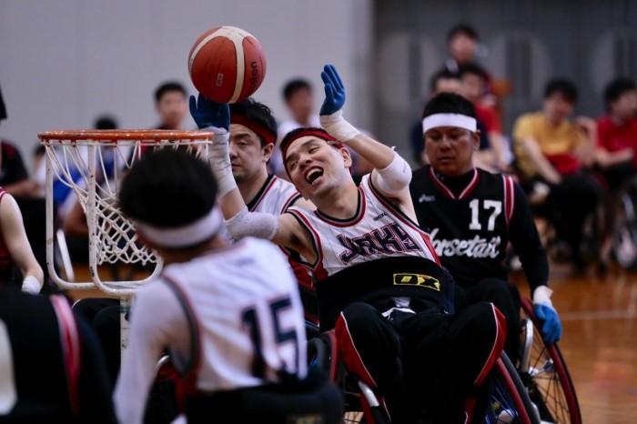 神奈川JUNKSの深澤康弘(12番 1.5 円内)がシュート。フリースローサークルの内側からシュートする選手はヘアバンドの色が赤。外側からシュートする選手は白