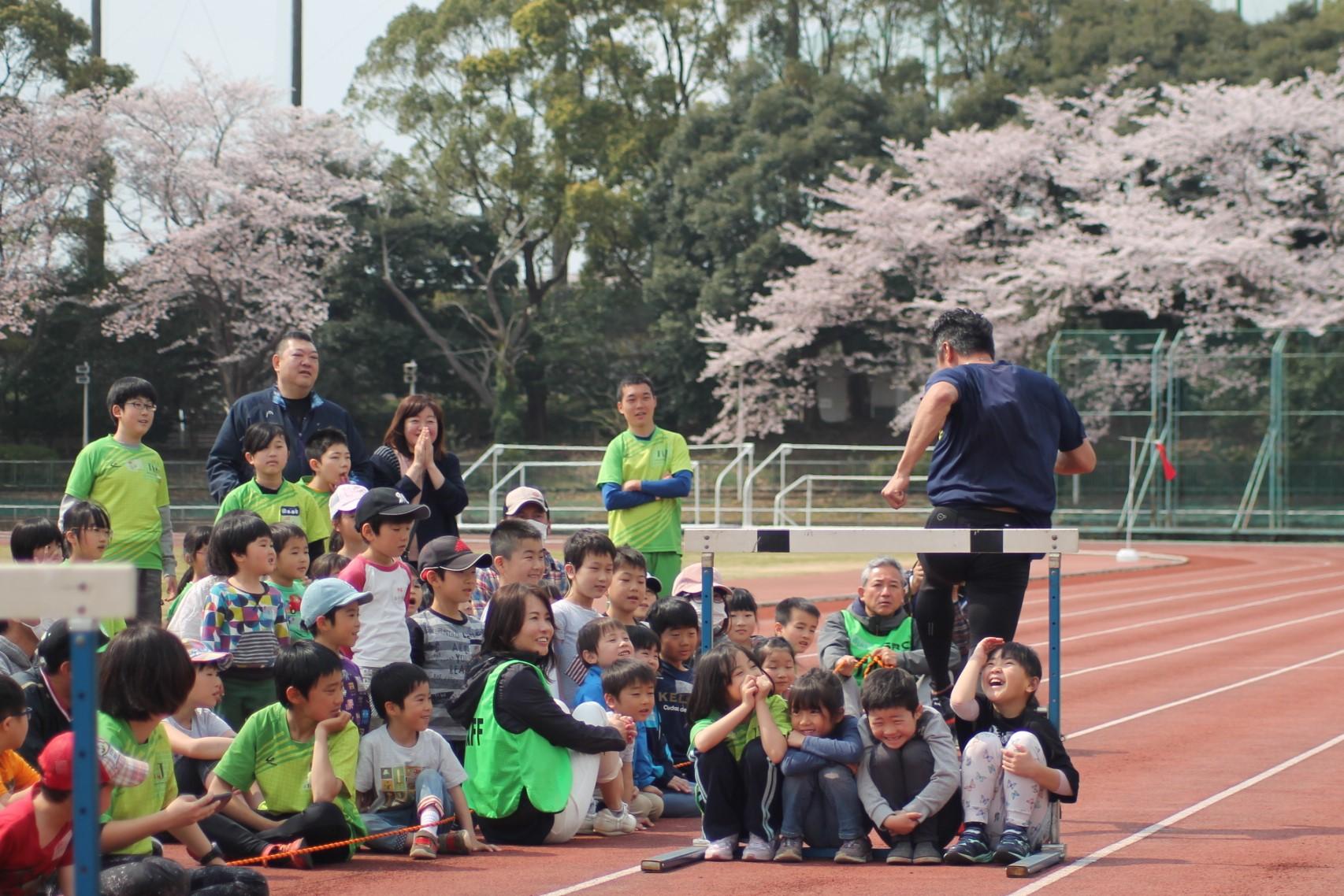 ハードルのデモンストレーションでは、短距離・ハードラーの吉岡康典が子どもたちを自分が飛ぶハードルの下に座らせ、飛び越えてみせた