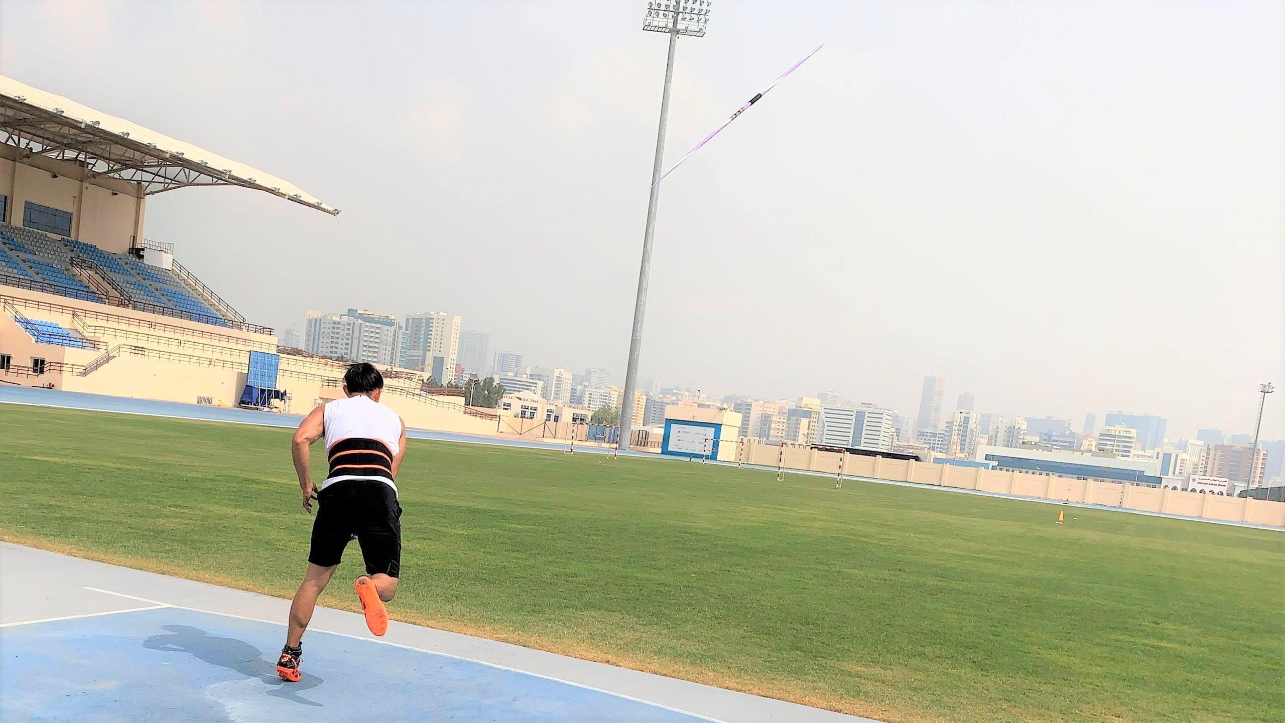 若生選手がドバイの陸上競技場でやりを投げた直後を後ろから撮影した画像